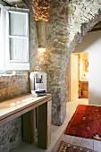 Rustikaler Durchgang in restauriertem Steinhaus mit Einblick in beleuchtetes Badezimmer