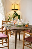 Place settings and candle lanterns on old wooden table