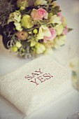 Ring cushion with motto 'SAY YES!' in front of bridal bouquet