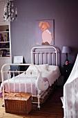 Weißes Metallbett an violetter Wand mit Hasenmotiv-Bild in Kinderzimmer mit nostalgischem Flair