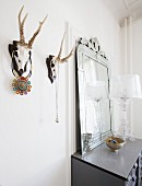 Hunting trophies used as jewellery racks next to chest of drawers with mirror on top