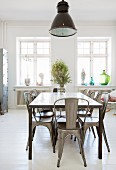 Metal chairs around dining table on white board floor