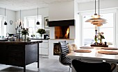 Dining area, fire in open fireplace and island counter made from old workbench in open-plan kitchen