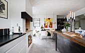 White kitchen counter next to fireplace, island counter made from old workbench in open-plan kitchen with dining area in background
