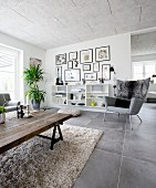 Rustic coffee table made from reclaimed wood and classic grey armchairs in front of open shelves in living room with grey tiled floor