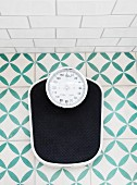 Bathroom scales on green and white patterned floor tiles