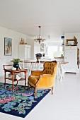 Gelber Barocksessel auf geblümtem Teppich vor Esstisch und Küche