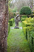 Clipped box hedges in autumnal garden with bust of woman on weathered plinth