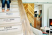 Restored wooden staircase with mottoes on risers and view of fire in stove and kitchen