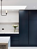 Purist kitchen with black fronts and marble worksurfaces