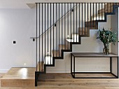 Cubist table below modern staircase with iron-rod balustrade