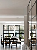 Floor-to-ceiling industrial windows and dining table in modern loft apartment