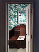 Blick in eine Toilette mit antikem Holz-WC und Dschungel-Tapete