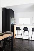 White kitchen counter and black bar stools on dark floor