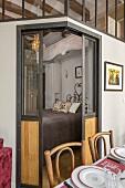 Geöffnete Schiebetüren und Blick in eingebautes Schlafzimmer von eklektischem Appartement