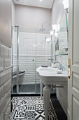 White sink and ornate black and white floor tiles in narrow bathroom