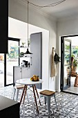Floral-patterned floor tiles and open terrace doors in black fitted kitchen