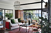 Couch, houseplants and tilted metal windows in eclectic lounge