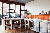 Recycled parquet floor, orange wall tiles and metal cabinets in open-plan kitchen of loft apartment
