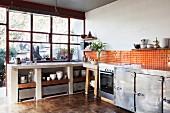 Offener Küchenbereich mit recyceltem Parkettboden, orangefarbenen Wandfliesen und Metallschränken