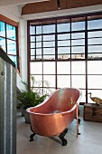 Free-standing vintage copper bathtub in front of wall of lattice windows