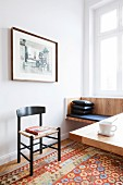 Black leather cushions on fitted bench below window and dining table in foreground on patterned rug
