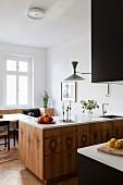 Kücheninsel mit Holzfronten und weißer Küchenarbeitsplatte vor hellem Essplatz