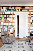 Comfortable armchair in front of bookcase built around white interior door