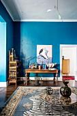 Wohnzimmer mit blauer Wand und Möbeln im Stilmix