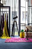 Femininer Industriestil: Bunte Garderobe vor Fabrikfenstern