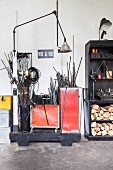 Metal rods in red containers and logs on black shelves in lamp manufactory