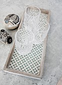Three crystal glasses on patterned concrete tray next to painted pebbles