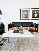 Couchtisch mit weißer Marmor-Tischplatte vor schwarzem Leder-Zweisitzer mit bunter Decke