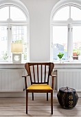 Exotic-wood armchair next to ethnic wicker basket in front of arched windows in renovated period apartment