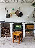 Firewood store, various wooden crates and pans hung on wall in rustic outdoor kitchen