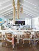 Long dining table and rattan chairs in beach house