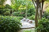 Sitzpoufs auf Holzterrasse im grünen Sommergarten