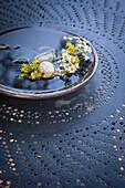 Schale mit Wasser, Steinen und Blüten auf einem Metalltisch