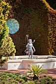 Neptun-Skulptur im Brunnen vor einer Hecke mit bemalter Schale