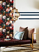 Elegant metal and leather couch with scatter cushions in front of floral wallpaper