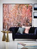 Dark velvet sofa below large picture of trees