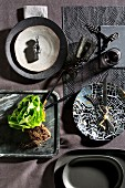 Crockery in earthy tones and black and lettuce on stone tray
