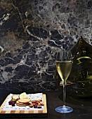 Glas Sekt und Snacks vor einer Kugelvase und Marmorwand