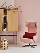 Pink armchair next to cabinet on metal legs in romantic Japanese interior