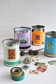 Tin cans covered with paper, postage stamps and washi tape