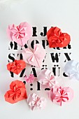 Origami hearts in pin and red on paper printed with letters