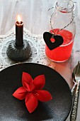Red origami flower on black plate and red drink in bottle