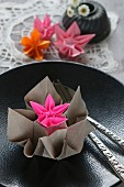 Origamiblumen aus Papier auf einem schwarzen Teller mit Relief