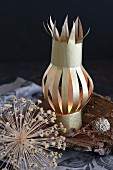 Small paper lantern on piece of bark next to dried flower heads