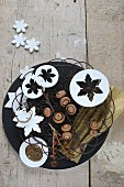 Wintry arrangement of metal basket, snowflakes and acorns